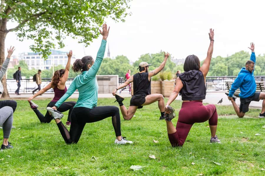 An outdoor yoga fitness class with 6 people.