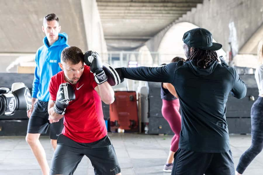 A personal trainer coaching two people boxing outdoors.