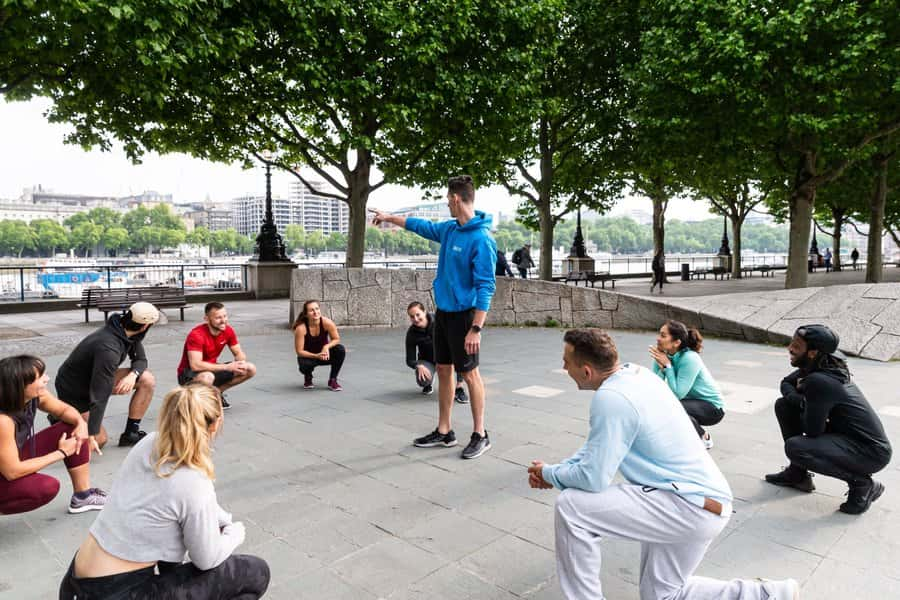 A group of people outdoors receiving instruction from a personal trainer.